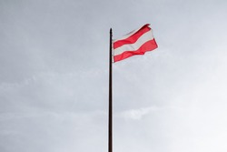 Wavy flag of Brno, Czech Republic / Czechia - flag post and flagpole with heraldic sign and symbol of city and town. Minimalist sky in the background.