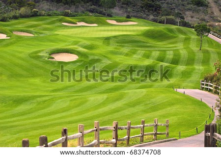 Wavy green golf field with a wooden fence