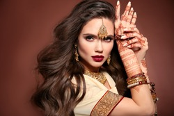 Wavy hair. Portrait of beautiful woman with indian jewelry. Young brunette model with Traditional Indian golden bijouterie set. Mehendi Henna painting on hand.