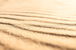 Wavy pattern sandy texture of clean beach sand surface. Coastline travel background with copy space, selective focus.