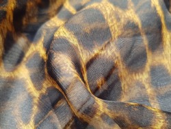 Wavy translucent fabric, with leopard print, in folds (texture).