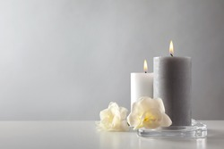 Wax candles and flowers in glass holder on table against light background. Space for text