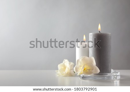 Wax candles and flowers in glass holder on table against light background. Space for text Photo stock ©