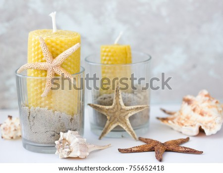 wax candles  in jars with sea sand, sea shells. Marine style home accessories for beach themed interior decorating