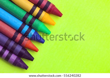 Wax crayons on yellow green background #556240282