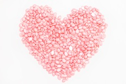 Wax for depilation of pink color. in the form of a heart. On white background. The concept of waxing, smooth skin.