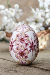 Wax painted egg  and plum cherry flowers  on wooden surface ;  geometric motifs  close-up