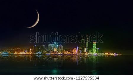 Waxing Crescent on beautiful night cityscape, view of Batumi city at night. Night reflections of lights in Black Sea port of Batumi, capital of Adjara. Georgia.