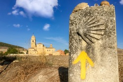 Way Marker Stone Post with Yellow Arrow Pilgrimage Symbol and View of Church in Castrojeriz on the Way of St James Pilgrim Trail Camino de Santiago