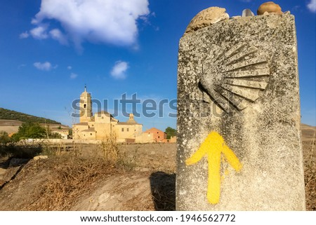 Way Marker Stone Post with Yellow Arrow Pilgrimage Symbol and View of Church in Castrojeriz on the Way of St James Pilgrim Trail Camino de Santiago Foto d'archivio ©