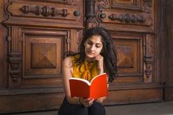 Way to Success. Power of Reading. A young beautiful East Indian American college student sitting by vintage style library door way, tilting head, hand touching chin, looking down, reading red book.