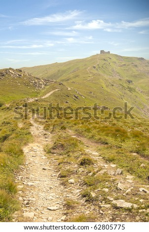 Way to the mountain peak with old castle ruins on the top