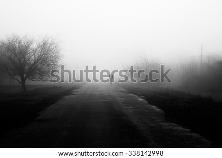 Wayfarer in fog. Silhouette of man walking on misty village road. Homecoming. Loneliness, 