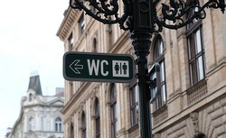 WC sign, logo of public toilets in the street against building background. For female, male. Public toilet sign on vintage street light pillar. Street lamp with wc symbols in downtown Prague.