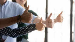 We all say yes! Close up shot of four young people workers clients of different gender ethnicity raising thumbs up showing general support acceptance recognition to company policy, service or product
