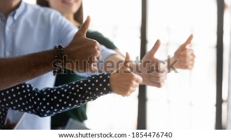 We all say yes! Close up shot of four young people workers clients of different gender ethnicity raising thumbs up showing general support acceptance recognition to company policy, service or product Foto stock ©