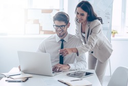 We already have great results! Young beautiful woman pointing at laptop with smile and discussing something with her coworker while standing at office