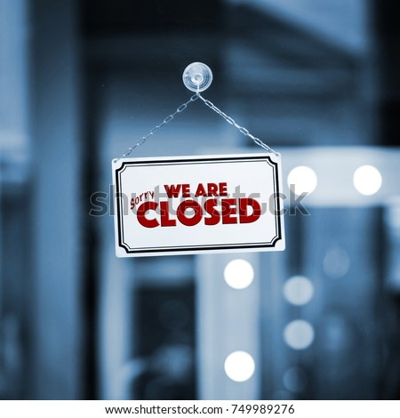 WE ARE CLOSED sign board through the glass of store window. Filtered image.
