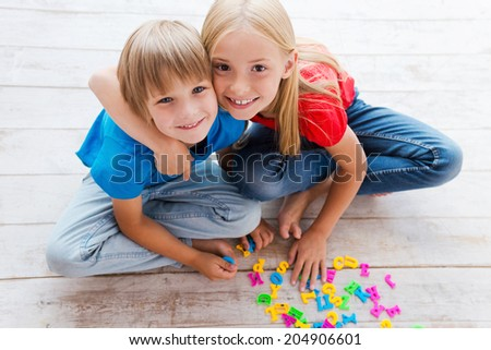 We are good friends! Top view of two cute little children looking at camera and smiling while sitting on the floor and playing with plastic colorful letters