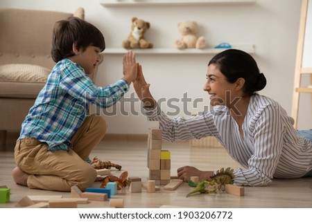 We are great team. Laughing indian mommy give high five to happy kid son celebrate building of high brick tower. Female babysitter construct from brick set with small boy on floor with heating system