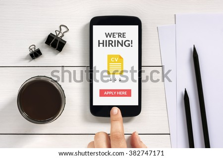 We are hiring apply now concept on smartphone screen with office objects on white wooden table. All screen content is designed by me.
