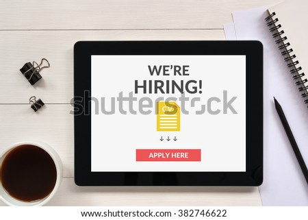 We are hiring apply now concept on tablet screen with office objects on white wooden table. All screen content is designed by me.