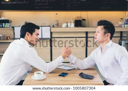 We are in a competitive business. We are in a competitive business. Two businessmen arm wrestling. Modern office background #1005807304