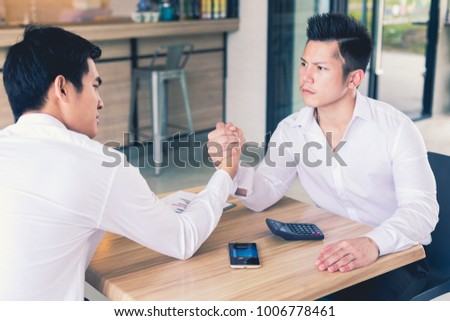 We are in a competitive business. We are in a competitive business. Two businessmen arm wrestling. Modern office background #1006778461
