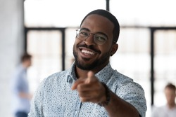 We are looking for you! Active cheerful young black male hr looking at camera pointing finger to spectator wanting get him to company, portrait of friendly african man leader selecting new team member