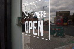 We are open door sign for cafe shop with the streets of London reflecting in the background