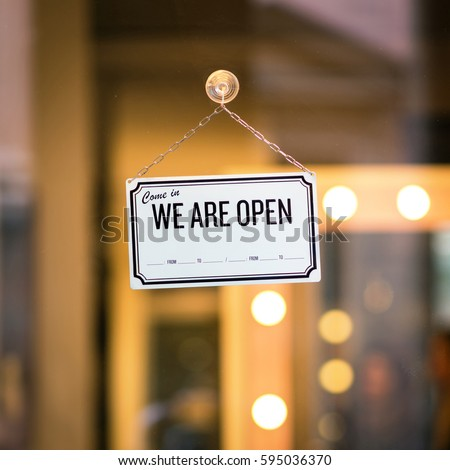 WE ARE OPEN sign board through the glass of store window. Filtered image. #595036370