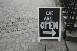 we are open - sign on a black chalkboard written in capital white letters.  The board stands on an empty street pavement with space. Stoned stairs with iron railings. Linz, Germany.