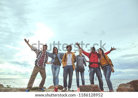 We are overjoyed. Full length portrait of team standing by sea and hugging while smiling