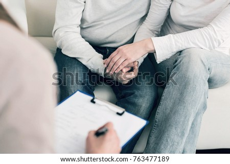 We are strong. Two people holding hands and sitting close to each other while consulting with their doctor