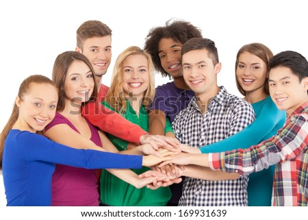 We are strong when we together. Cheerful group of multi-ethnic people holding hands together and smiling at camera while standing isolated on white