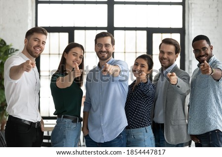 We are waiting for you! Group portrait of friendly successful diverse staff multiethnic teammates young men and women standing in row at office pointing fingers at camera choosing new colleague client