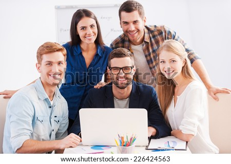 We are working as team. Group of cheerful business people in smart casual wear working together and smiling