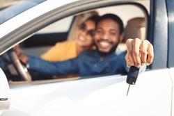 We bought car. Happy couple showing car key, sitting in new car, focus on hand