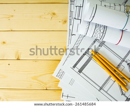 We build a building. House construction. Many drawings for building and pencils on a wooden background.