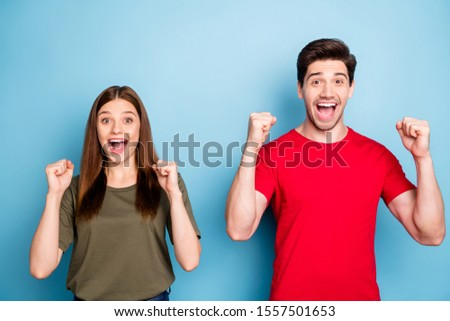 We champions omg! Portrait of positive cheerful married couple hear wonderful lottery winning news raise fists scream wow wear green red t-shirt isolated over blue color background