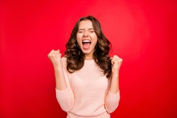 We did it! Portrait of closed eyes raised fists up woman in casual wear isolated on vivid red background with closed eyes and wide open mouth