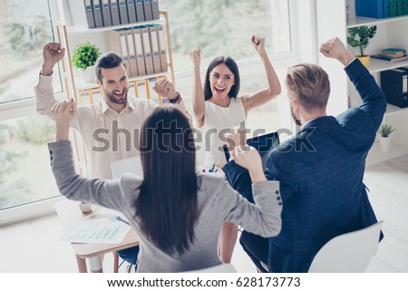 We did it! Success and winning concept - happy business team with raised up hands in light modern workstation, celebrating the breakthrough in their company #628173773