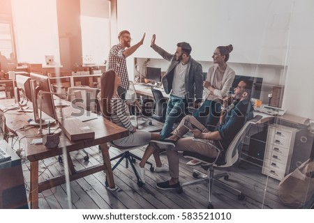 We did it! Two cheerful young business people giving high-five while their colleagues looking at them and smiling  - Shutterstock ID 583521010