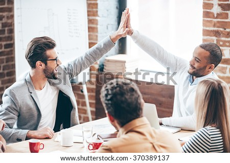 We did it! Two young men doing high-five while their coworkers sitting at the office table #370389137