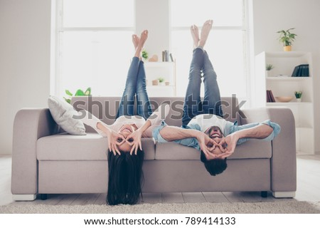 We go crazy and have fun together! Beautiful cheerful delightful humorous couple of two lovers clothed in casual denim outwear, demonstrating binoculars using hands, lying upside-down #789414133
