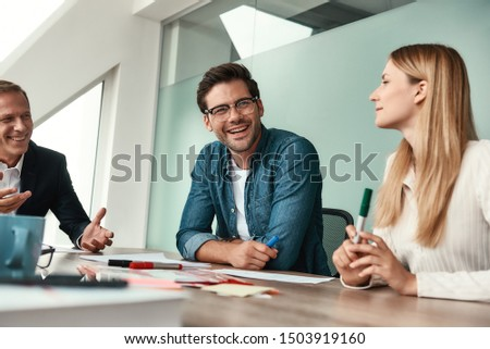 We have great results Young handsome man in eyeglasses discussing something with colleagues and smiling while sitting in the modern office
