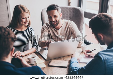 We have positive dynamic! Young handsome man pointing at his laptop with smile while sitting at the office table on business meeting with his coworkers