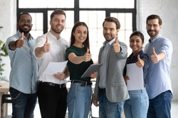 We like it! Group portrait of young multiethnic employees skilled in profession standing together at office hall in workday, smiling looking at camera raising thumbs up recommend to join their team