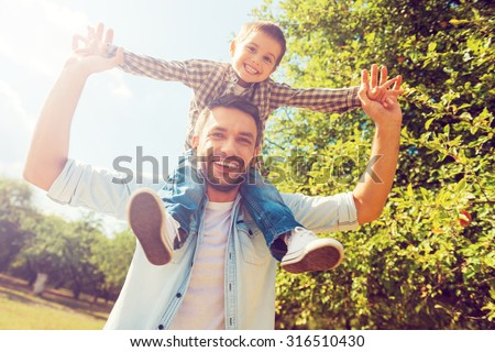 We like spending time together! Low angle view of happy little boy stretching out hands while his father carrying him on shoulders stock photo