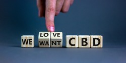 We love CBD, cannabidiol symbol. Hand turns cubes and changes words 'We want CBD' to 'We love CBD'. Beautiful grey background, copy space. Medical and we love CBD cannabidiol concept.